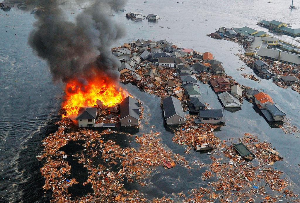 Những ngôi nhà ở Natori, tỉnh Fukushima, bốc cháy trong thảm hoạ kép. Ở nhiều khu vực khác, sân bay, cảng, nhà cửa đều chìm ngập dưới nước.