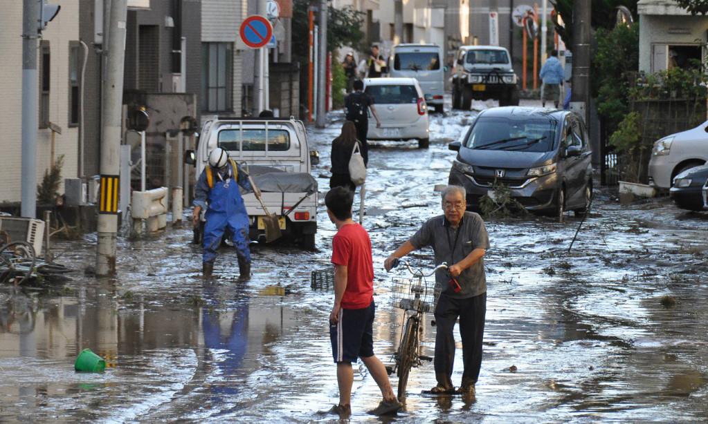 Dân địa phương dọn dẹp đường phố sau trận lụt tại thành phố Kawasaki sáng nay.
